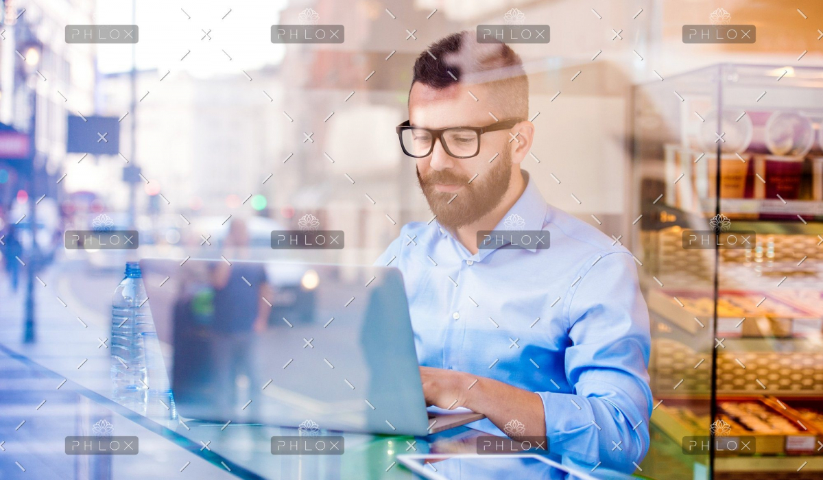 demo-attachment-146-Hipster-manager-in-cafe-working-on-laptop-by-window