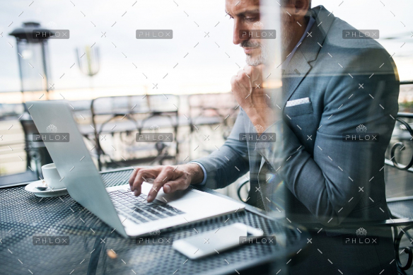 demo-attachment-33-Mature-businessman-with-laptop-outside-a-cafe.